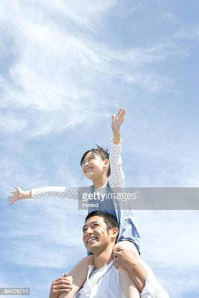 Girl smiling on father's shoulders