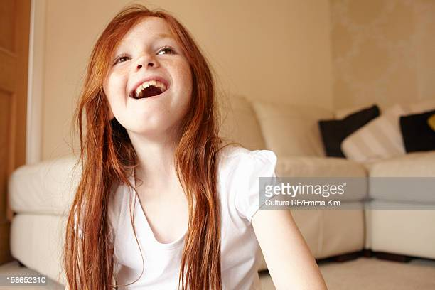 girl smiling on living room floor - redhead girl stock photos and pictures