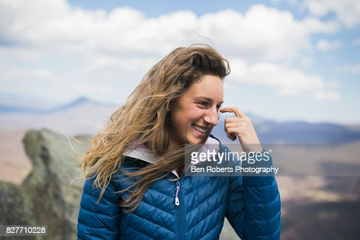 Girl smiling on windy mountain