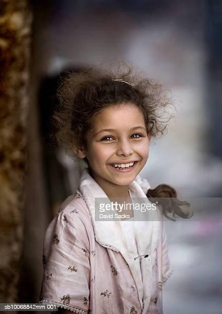 Girl (6-7) smiling outdoors, portrait
