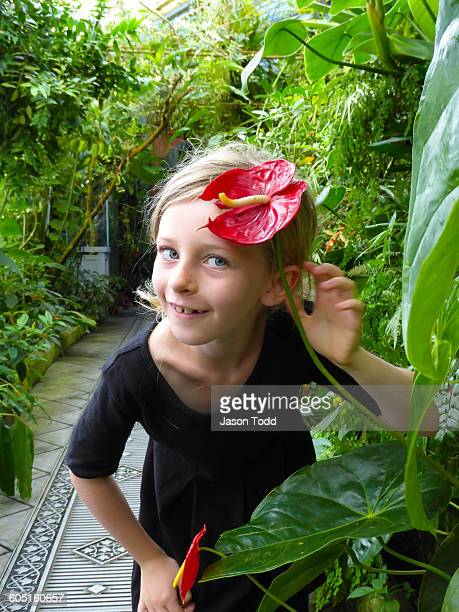 Girl smiling pretending to put flower in her hair