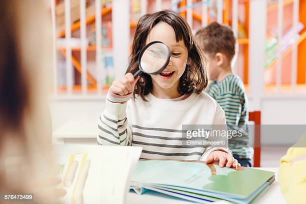 girl smiling reading book with magnifying glass - vorschulkind stock-fotos und bilder