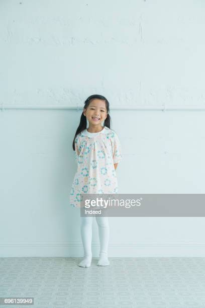 girl smiling, standing by wall - girls ストックフォトと画像