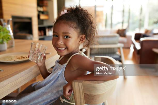 Girl smiling to camera and holding glass of water