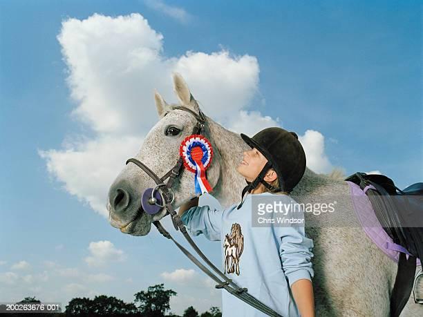 Girl (10-12) smiling up at horse wearing rosette