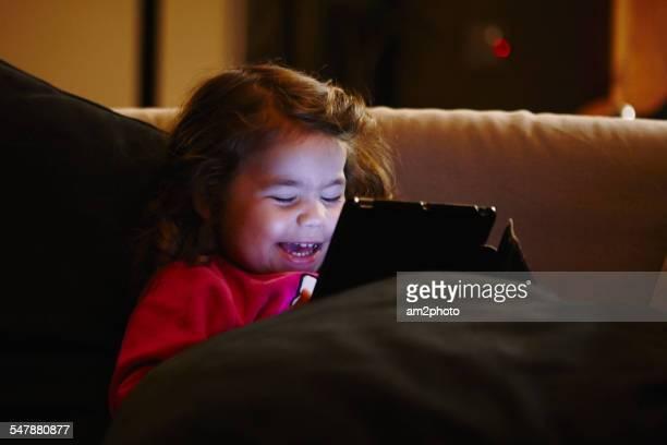 Girl smiling usin digital tablet in the sofa
