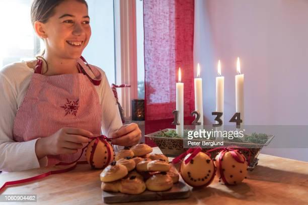 mädchen lächelnd bei der herstellung von weihnachtsschmuck - gewürznelke stock-fotos und bilder