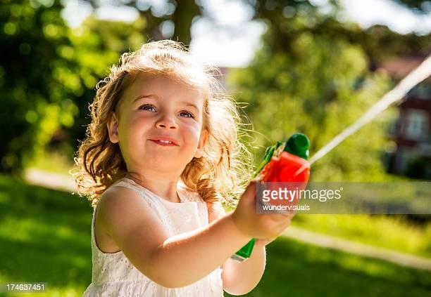 Girl smiling while splashing water with squirt gun