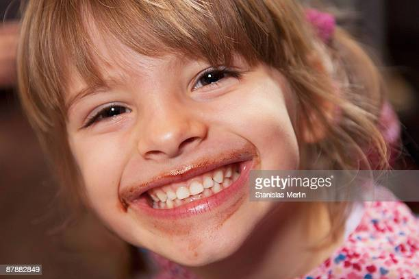 Girl smiling with chocolate around mouth