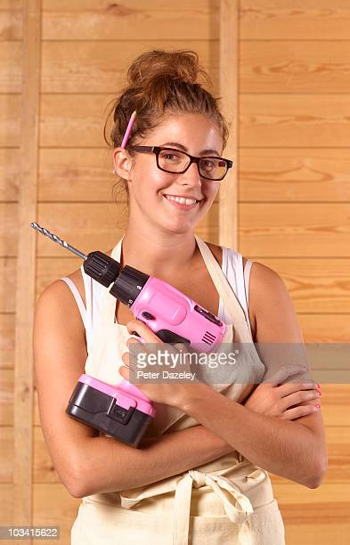 Girl smiling with pink power drill