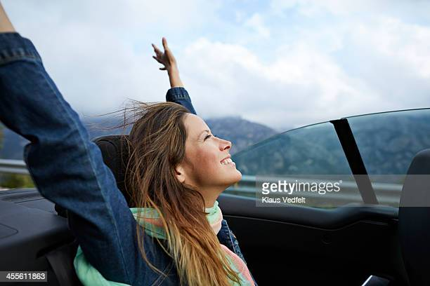 Girl smiling with raised arms, riding car