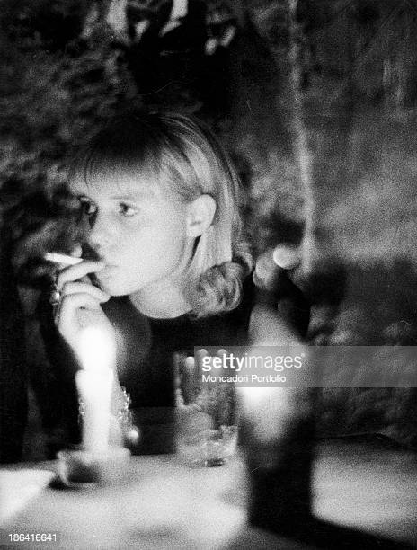 A girl smoking a cigarette during a cocktail party in a club of Copenhagen Copenhagen 1960s