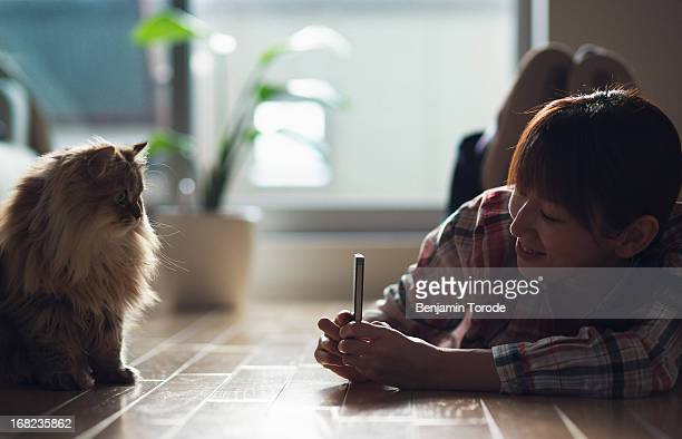 Girl snapping photo of cat with smartphone