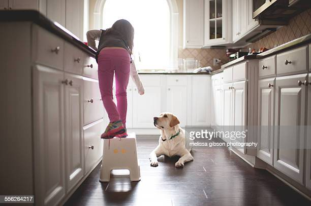 Girl sneaks dog a snack