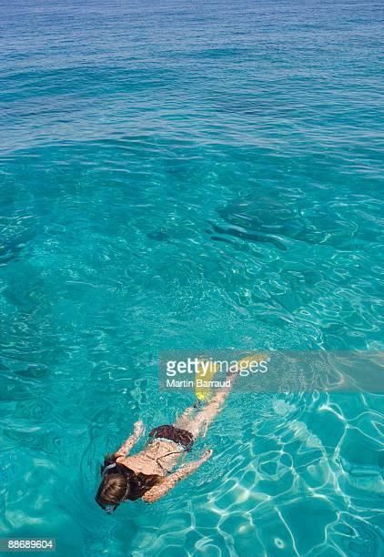 Girl snorkeling in ocean