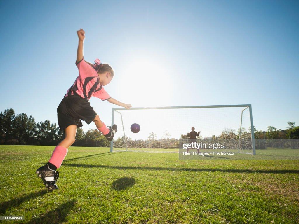Girl soccer player kicking soccer ball at net : Stock Photo