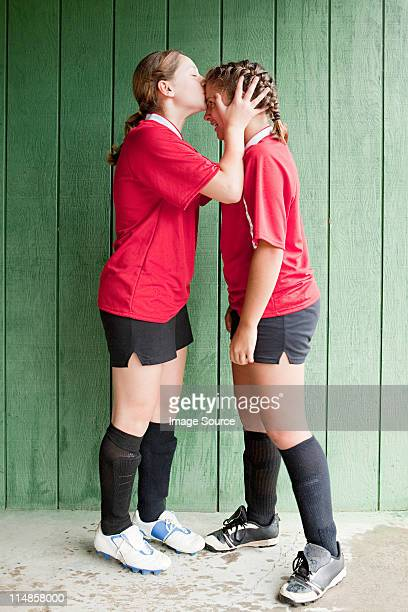 girl soccer player kissing teammate - only teenage girls stock pictures, royalty-free photos & images