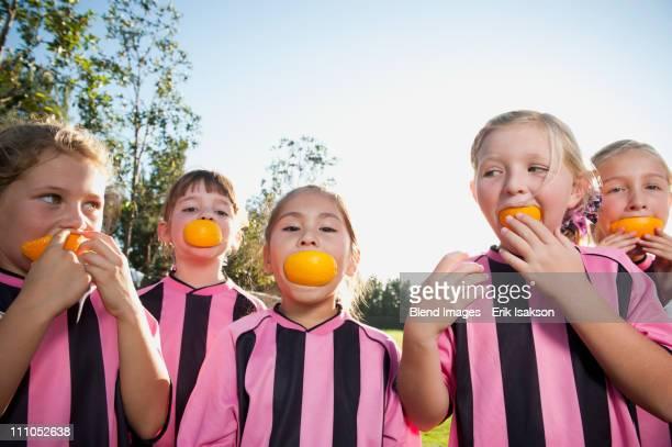 Girl soccer players eating orange slices