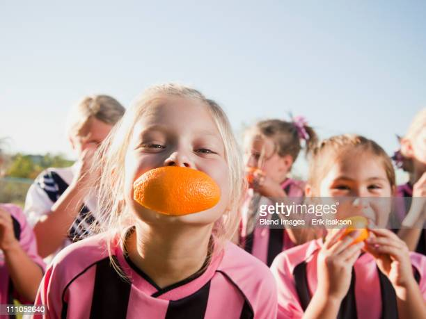 Girl soccer players eating orange slices