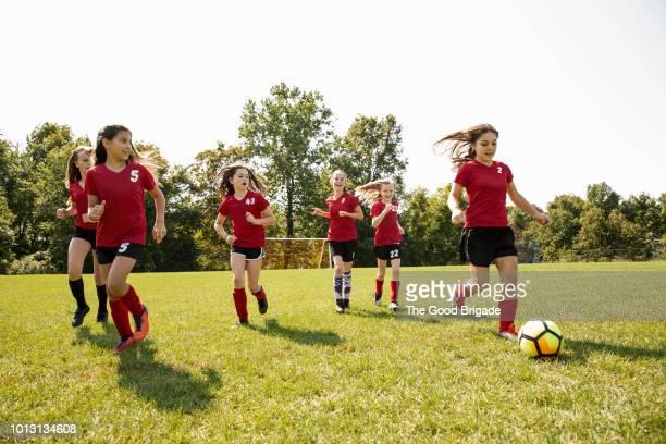 girl soccer team practicing on grassy field - 足球 團體運動 個照片及圖片檔