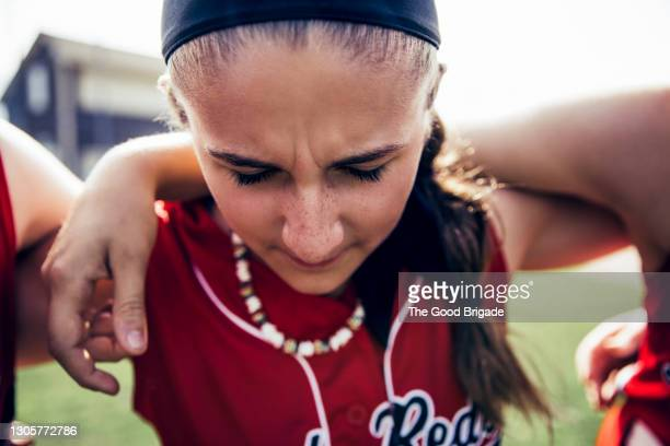 girl softball team huddle on field before game - baseball strip stock pictures, royalty-free photos & images