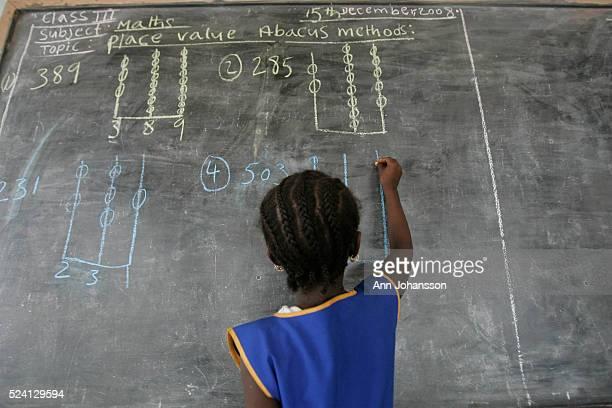 Girl solves a problem on a school blackboard in Kenema, Sierra Leone.