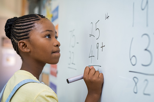 Girl solving mathematical addition 950609102