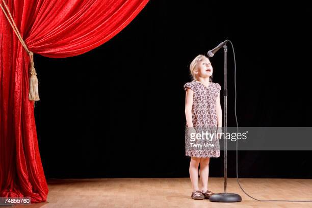girl speaking into microphone on stage - stage performance space stock pictures, royalty-free photos & images