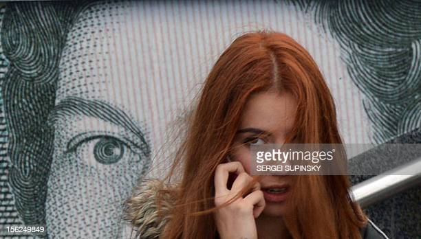A girl speaks on a mobile phone as she stands in front of an advertising placard depicting British pounds on a warm autumn day in the Ukrainian...