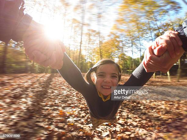 Girl spin holding hand to dad on POV autumn view.