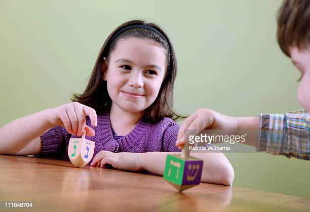 girl spinning a dreidel. - dreidel stock photos and pictures