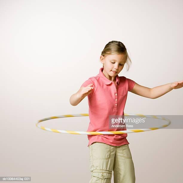 Girl (6-7) spinning in hula hoop
