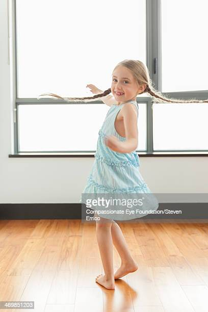 Girl (6-7) spinning indoors