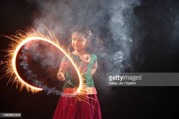 girl spinning sparkler while standing against black background - diwali stock pictures, royalty-free photos & images