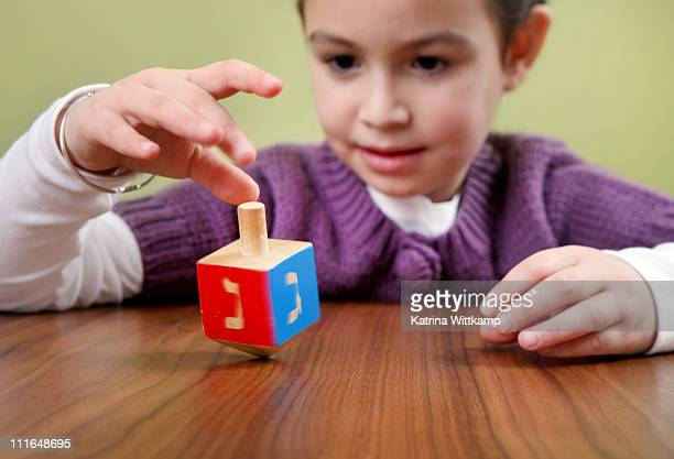girl spins a dreidel. - dreidel stock photos and pictures