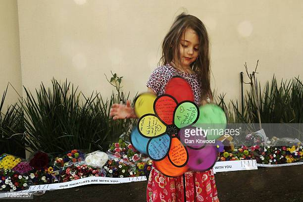 A girl spins a pinwheel with messages of support for Nelson Mandela outside his residence on July 3 2013 in Houghton Estate South Africa The...