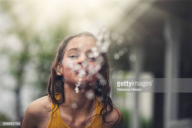 girl spitting out water towards camera