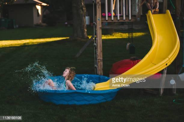 Girl splashing into kiddie pool