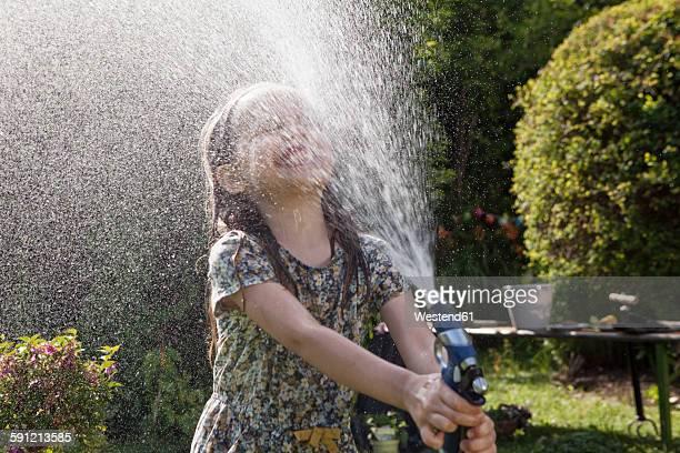 Girl splashing with water in garden