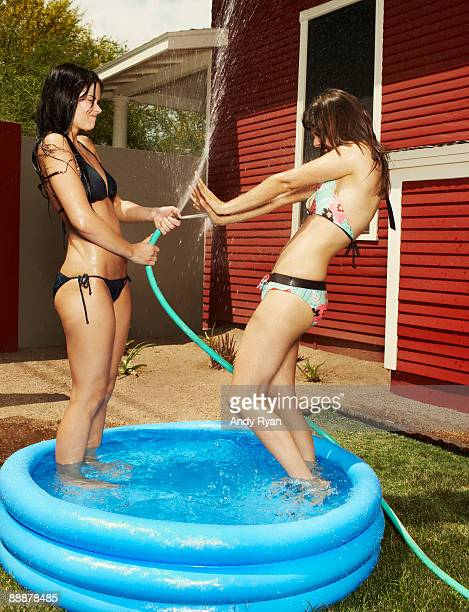Girl Spraying Friend With Hose in Kiddie Pool