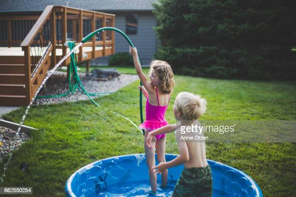 Girl Spraying Garden Hose