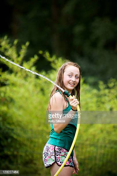 Girl spraying water in yard