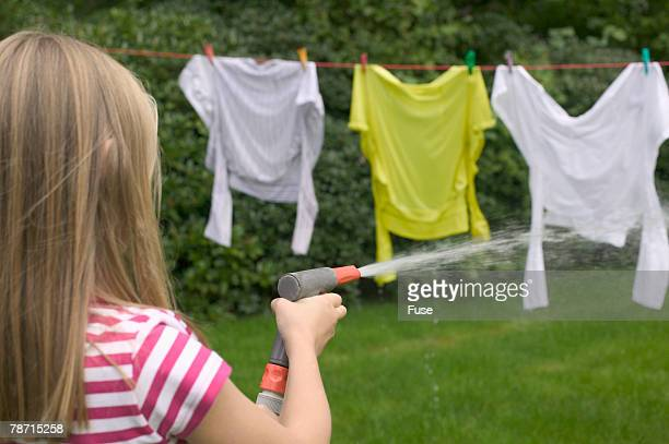 Girl spraying water with garden hose on clothes hanging on clothes line