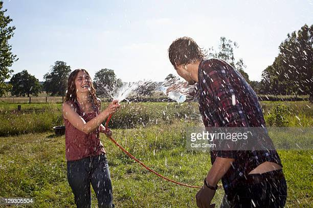 girl sprays guy with hose on field - nass stock-fotos und bilder