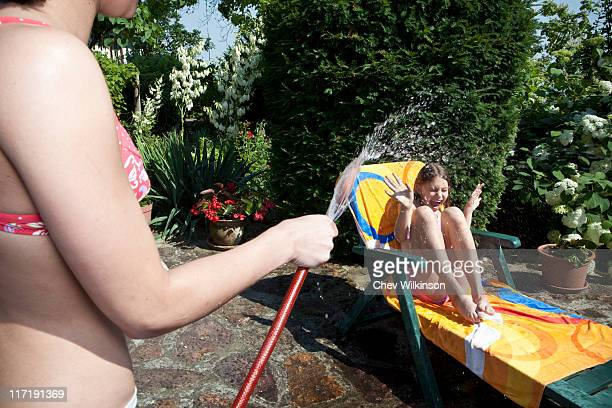 Girl sprays water on sister