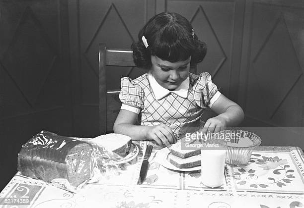 Girl (6-7) spreading butter on slice of toast, (B&W)