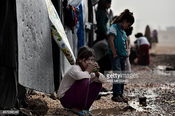 Girl squats outside tents at a Syrian Kurdish refugee camp in the Turkish town of Suruc in the Sanliurfa province on October 11, 2014. About 300,000...