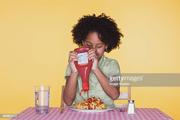 girl squeezing ketchup onto curly fries - ketchup stock photos and pictures