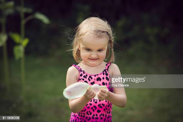 Girl (4-5) squeezing water balloon and grimacing with anticipation