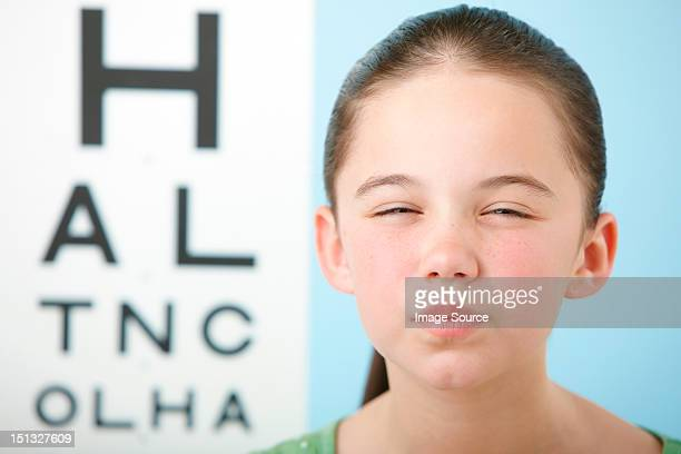 Girl squinting with eye chart in background